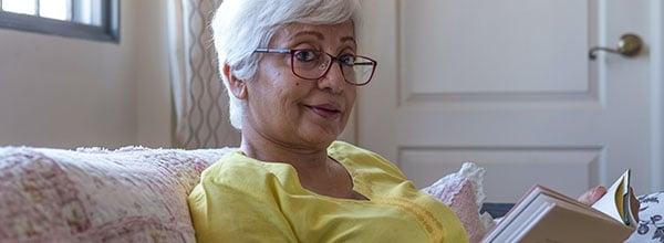 Senior lady enjoying her book, maintaining her brain health and mental agility
